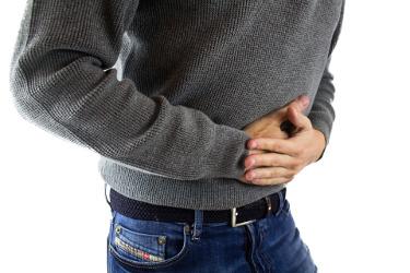 Kuvassa mies pitelee vatsaansa kipujen vuoksi