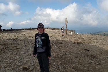 Nainen seisoo loivan mäen alapuolella ja katsoo lippalakki päässä hymyillen kohti kameraa.
