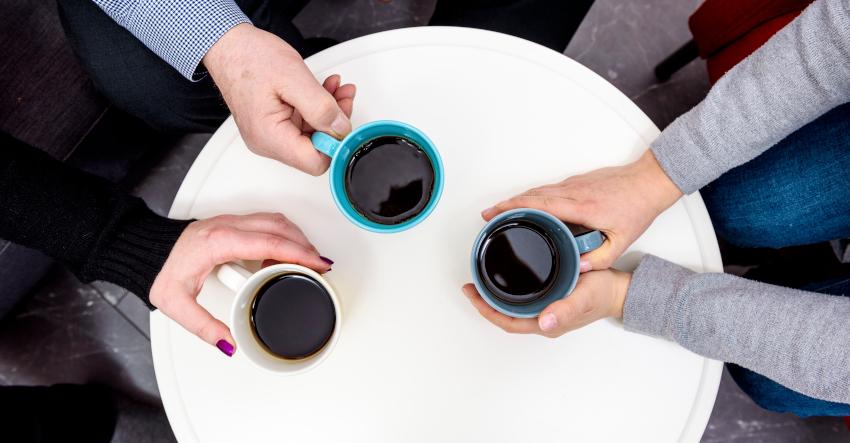 Ylhäällä kuvatun pöydän päällä on kolme kahvikuppia. Kuvassa näkyvät myös kupeista kiinni pitävien ihmisten kädet.