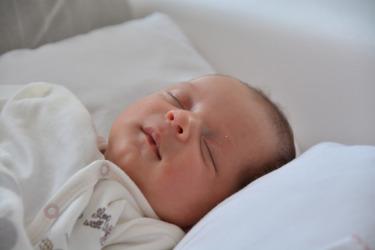 Nukkuva vauva, josta näkyvät vain kasvot ja rintakehä.