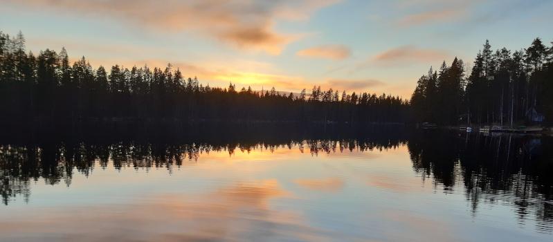Auringonlasku on värjännyt taivaan punaiseksi. Värit ja taivaanrannan metsikkö heijastuvat järven pintaan.