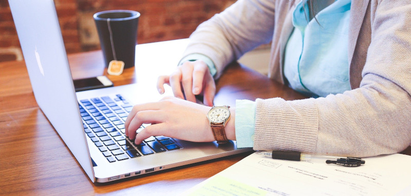 Opiskelijan sormet ovat tietokoneen näppäimistöllä. Tietokoneen vieressä on teekuppi ja oikeassa alakulmassa näkyy lisäksi muistiinpanovihko ja