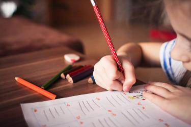 Nuori lapsi piirtää paperille. Hänestä näkyy kuvassa vain nenänpää ja kädet, joissa toisessa on kynä.