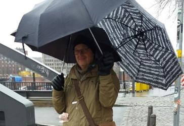 Mies pitelee käsissään kolmea sateenvarjoa ja katsoo kohti kameraa