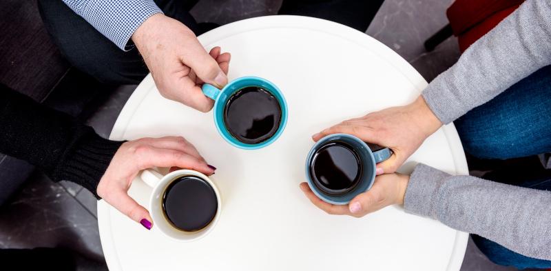 Pöydän päällä on kolme kahvikuppia, joita pitelevät kädet.