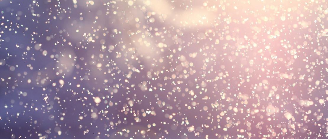 Lähikuva lumisateesta, hiutaleet kimmeltävät taustalta paistavaa auringonvaloa vasten.